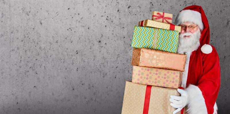 Santa Claus som rymmer en bunt av julklappar mot en vanlig bakgrund med kopieringsutrymme arkivfoton