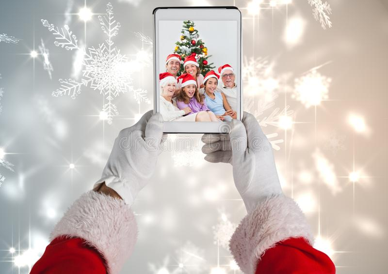Santa Claus som rymmer en digital minnestavla med fotoet av julfamiljen royaltyfri foto