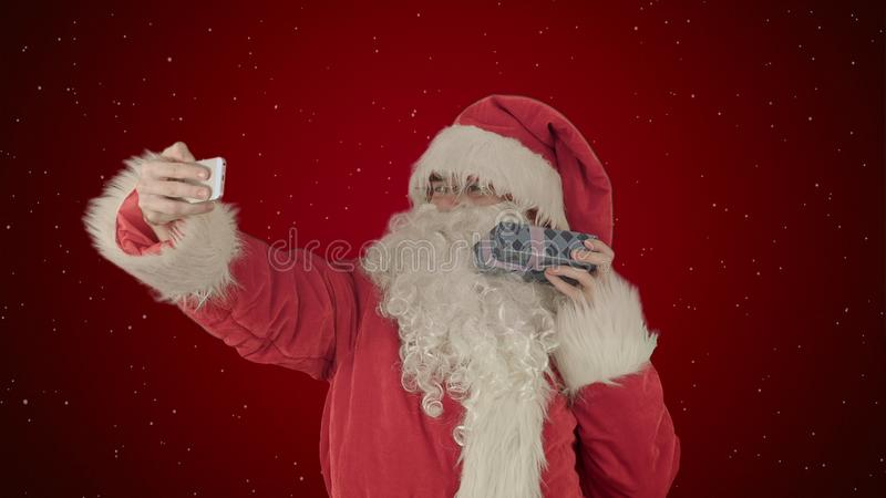 Santa Claus som rymmer en stor gåva som gör en selfie på smartphonen på röd bakgrund med snö arkivbild