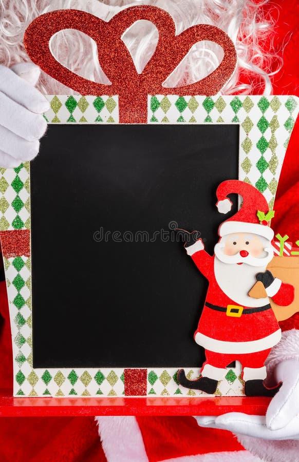 Santa Claus som rymmer ett tom jul dekorerat kritabräde bra för texter arkivbild