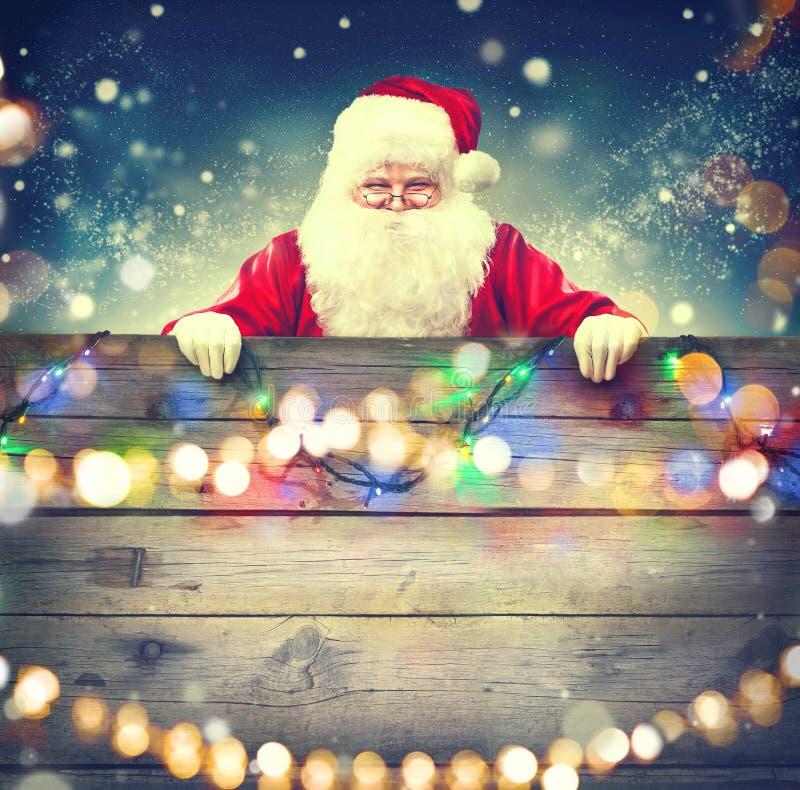 Santa Claus som rymmer träbanerbakgrund royaltyfria bilder
