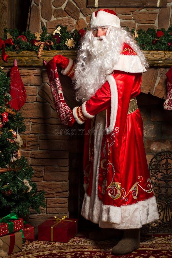 Santa Claus som sätter gåvor i julstrumpor på spisen arkivbilder