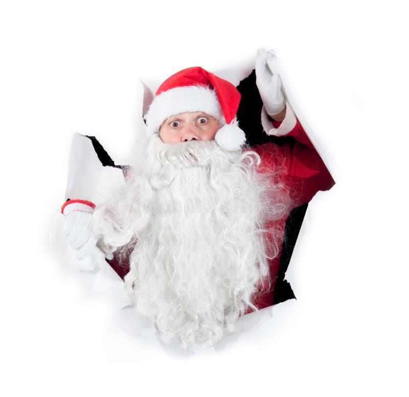 Santa Claus som ser till och med hålet royaltyfria foton