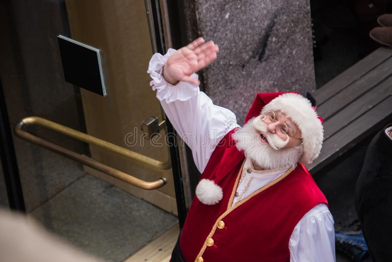 Santa Claus som ser upp och vinkar, som sett från över arkivfoton