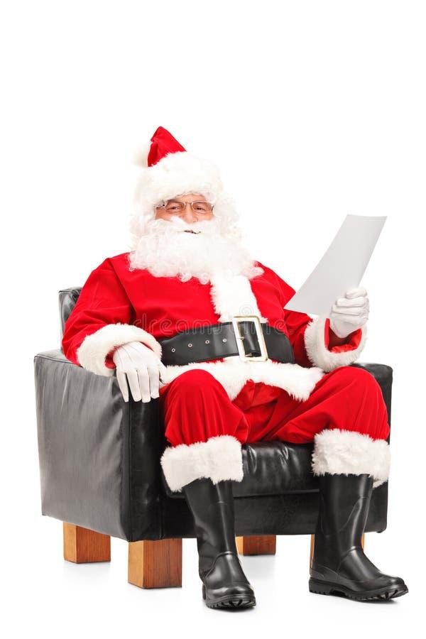 Santa Claus som sitter i fåtölj och läser bokstaven arkivbild