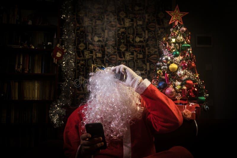 Santa Claus som vaping den elektroniska cigaretten som kläs som traditionell jultomten på en mörk tonad bakgrund med vapemoln Sel arkivbild