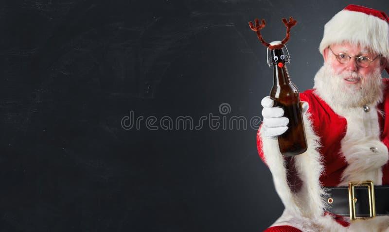 Santa Claus soulevant un pain grillé de Noël avec une bouteille de bière décorée des andouillers de cerfs communs au-dessus de gr images stock