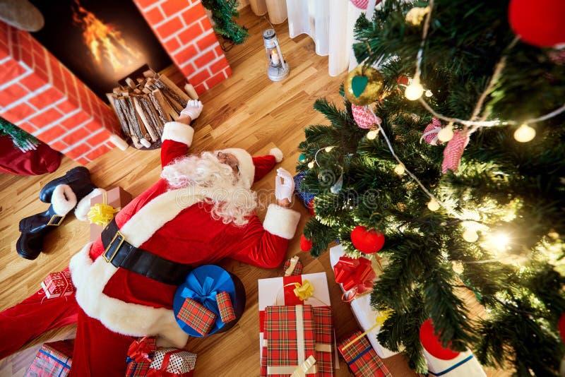 Santa Claus sover, tröttat som dricker i ett rum nära fireplaen royaltyfri fotografi