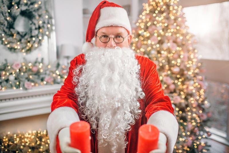 Santa Claus står bara i rum och rymmer två röda stearinljus i habds Han visar dem på kamera Mannen är allvarlig och arkivbild