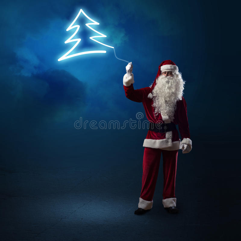 Santa Claus sta tenendo un albero di Natale brillante immagini stock libere da diritti