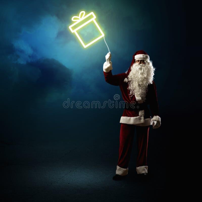 Santa Claus sta tenendo un regalo brillante fotografia stock