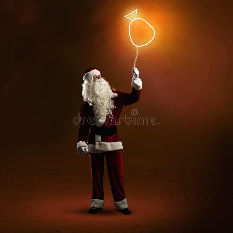 Santa Claus sta tenendo una borsa brillante fotografia stock libera da diritti