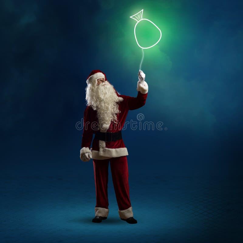 Santa Claus sta tenendo una borsa brillante immagini stock