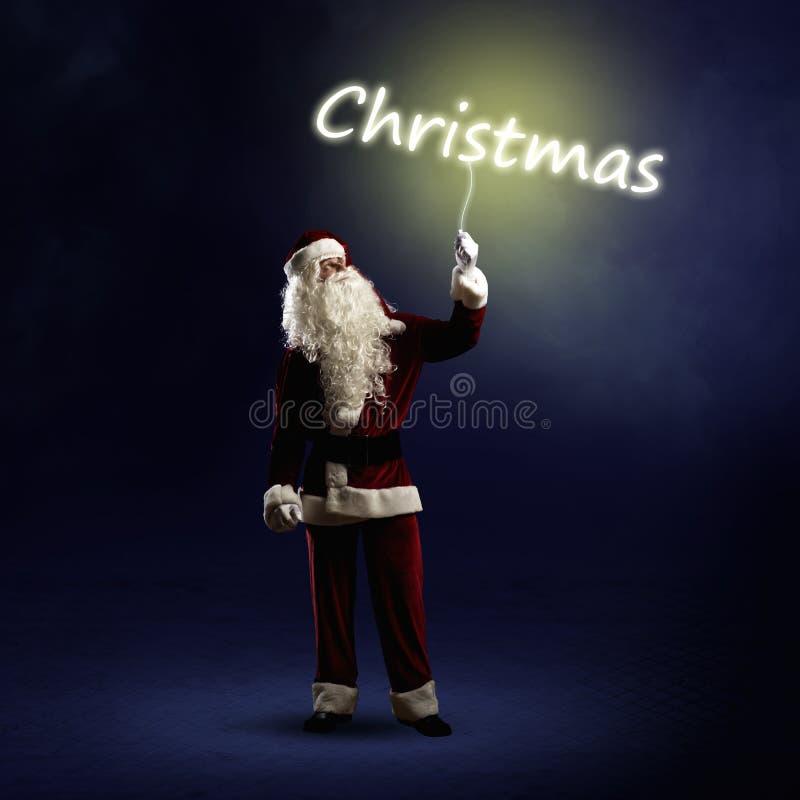 Santa Claus sta tenendo una parola brillante di Natale immagini stock