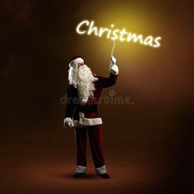 Santa Claus sta tenendo una parola brillante di Natale fotografia stock
