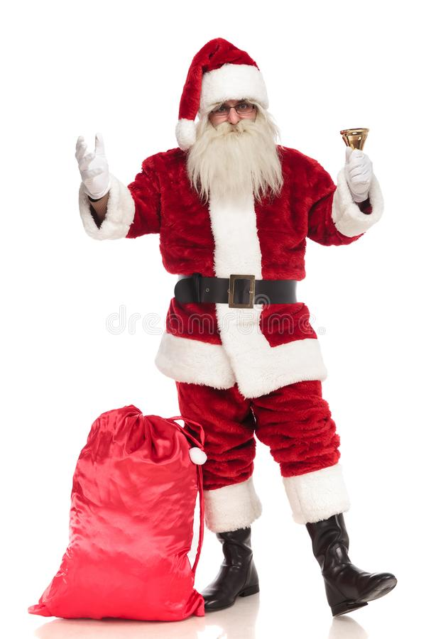 Santa claus standing with sack near leg rings his bell royalty free stock photos