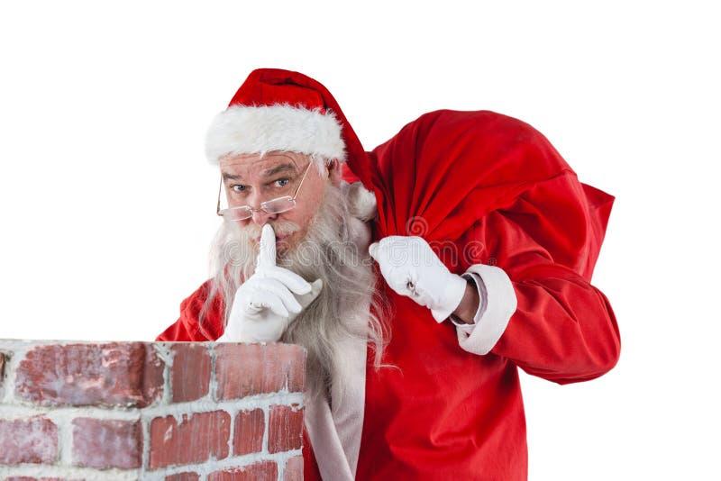 Santa Claus stoi obok kominu z palcem na wargach zdjęcia stock