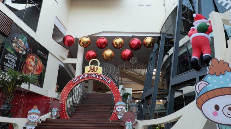 Santa Claus sube la pared de un centro comercial Decoraciones festivas de la Navidad Verano imagen de archivo libre de regalías