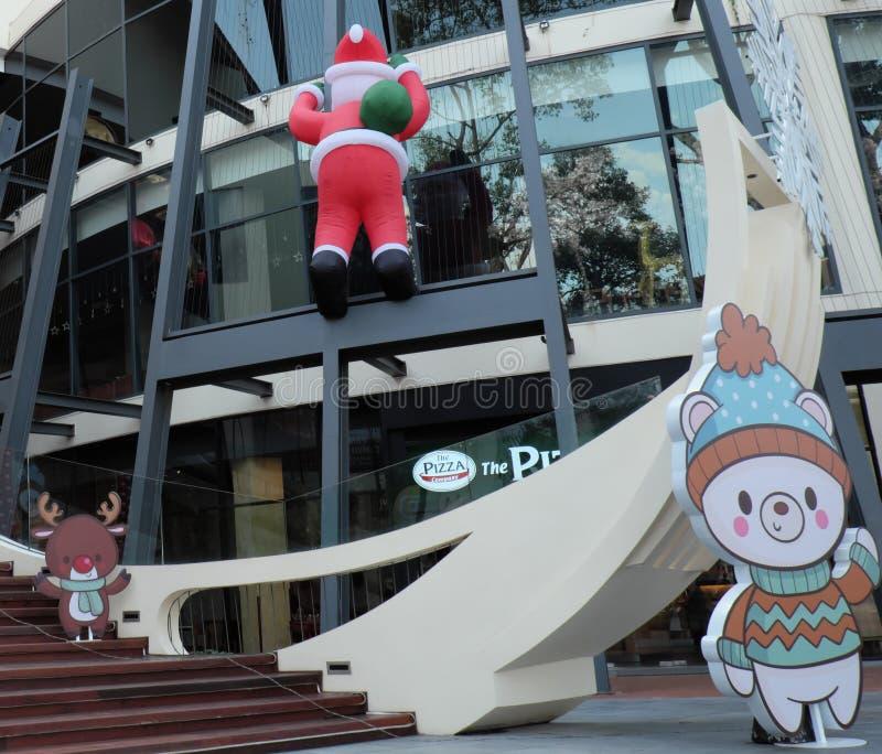 Santa Claus sube la pared de un centro comercial Decoraciones festivas de la Navidad Verano fotografía de archivo libre de regalías