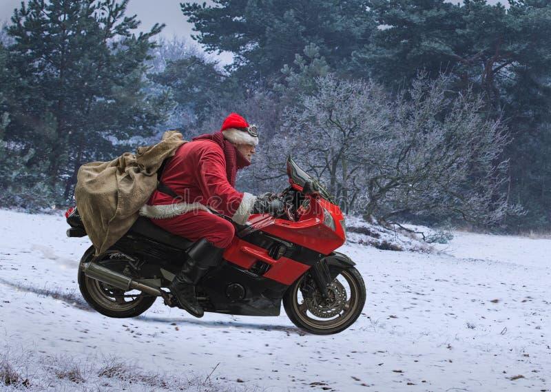 Santa Claus sur la moto rouge avec un sac conduisant le long de l'hiver s image stock