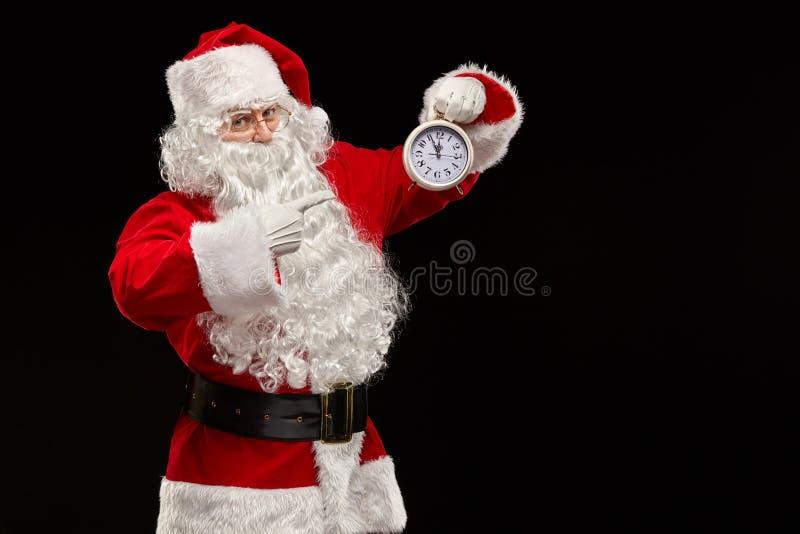 Santa Claus sur un fond de noir dirige son doigt à l'horloge Concept de Noël photographie stock libre de droits