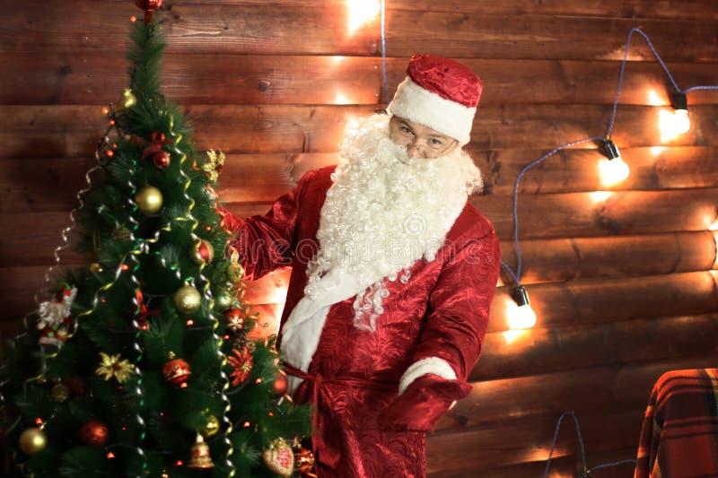 Santa Claus tänder ljusen på julgranen royaltyfri fotografi