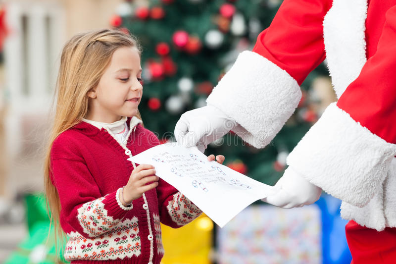 Santa Claus Taking Letter From Girl royalty-vrije stock afbeelding