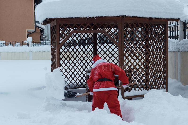 Santa claus taking with shovel snow away to make the way free in. Front of wooden house stock images
