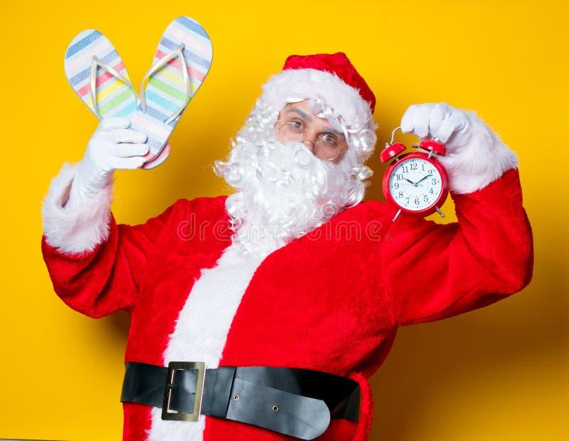 Santa Claus tenant les bascules électroniques et le réveil images libres de droits