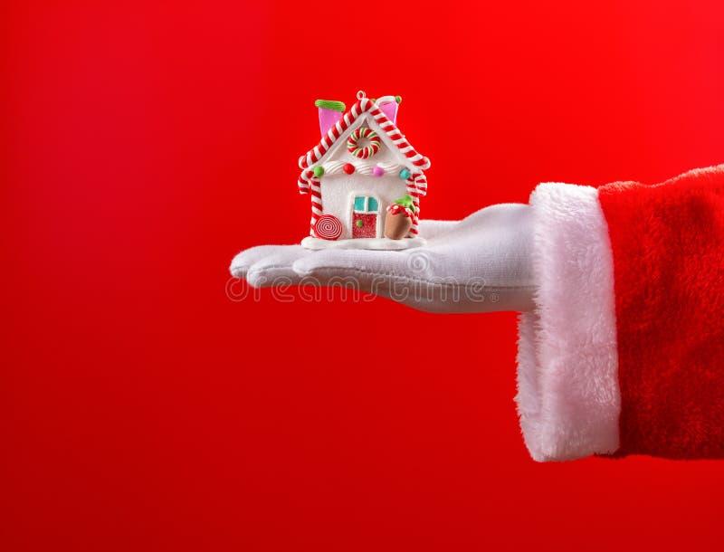 Santa Claus tenant un modèle de maison avec la décoration de Noël images stock