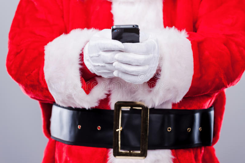Santa Claus texting. Close-up of Traditional Santa Claus holding mobile phone while standing against grey background stock photo