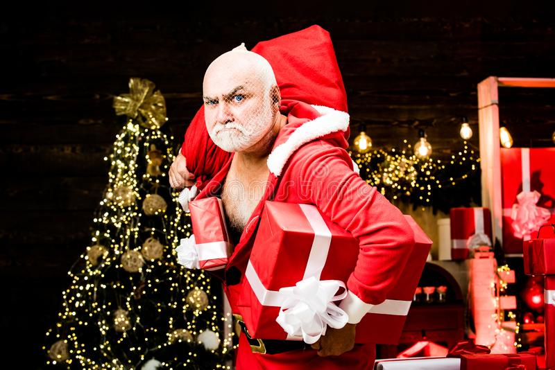 Santa Claus thief with a bag of christmas gifts. Thief Santa with bag on christmas background. Best prices for winter royalty free stock image