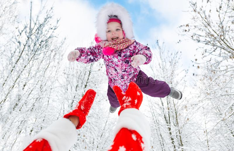 Santa Claus throws up overhead cute little girl in winter forest on Christmas royalty free stock photography