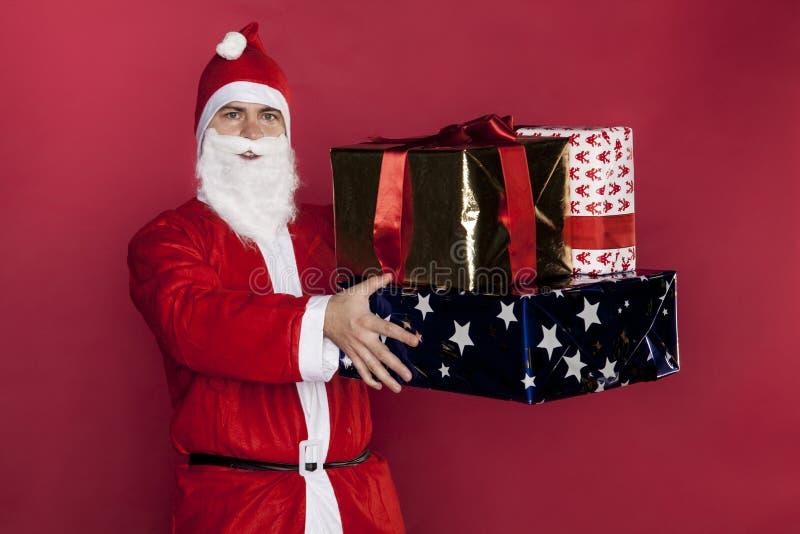 Santa Claus tiene i lotti dei presente in sue mani fotografia stock