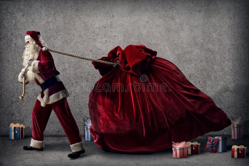 Santa Claus tira una borsa enorme dei regali immagini stock