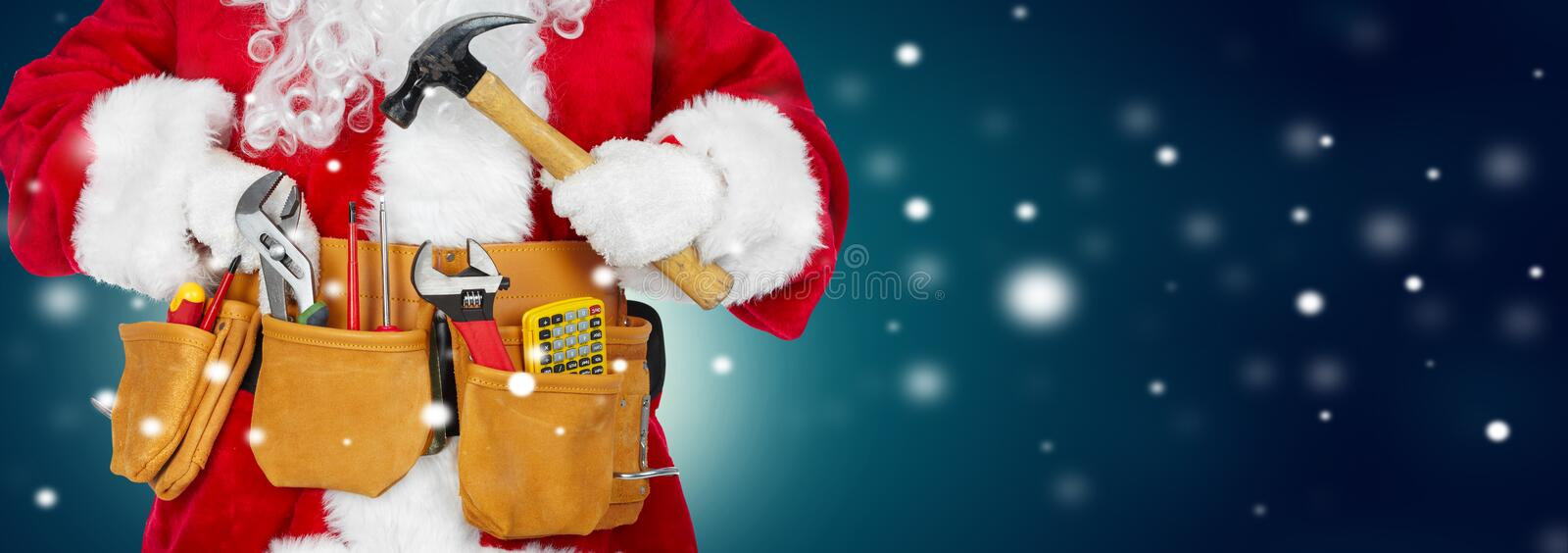 Santa Claus with a tool belt on winter background stock images