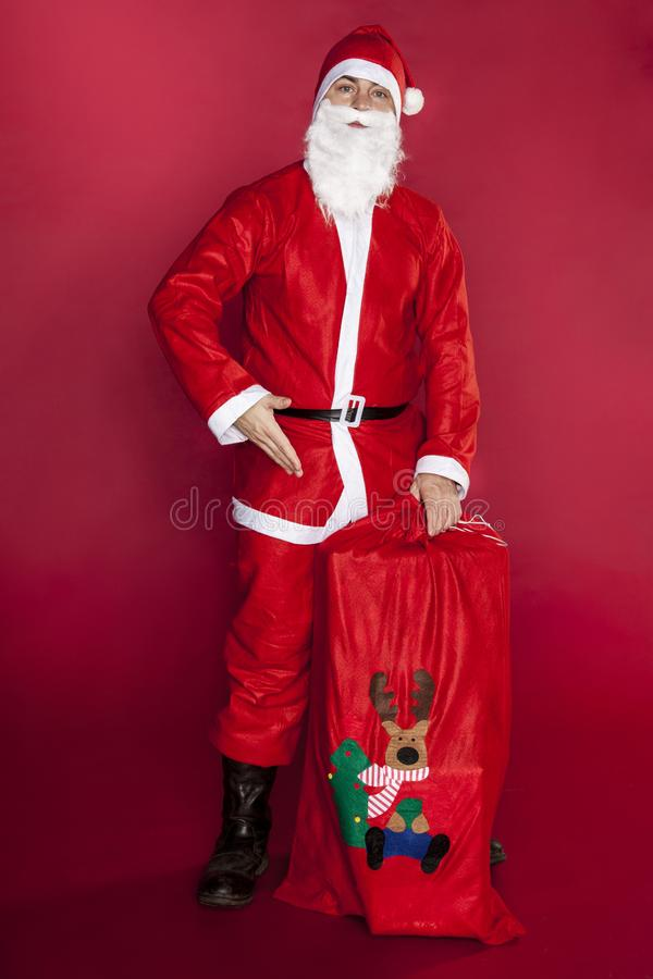 Santa Claus toont een zak wordt gevuld die met voorstelt royalty-vrije stock afbeelding