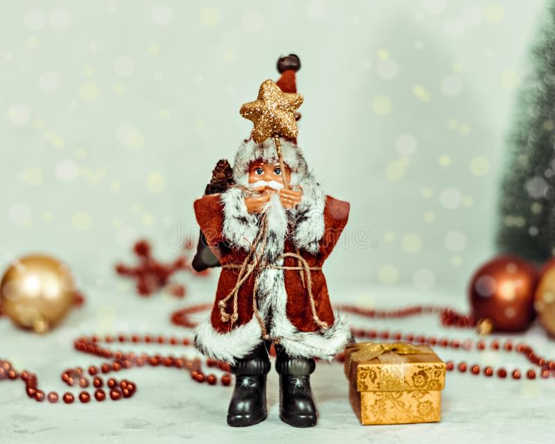 Santa Claus toy brings Christmas tree at blue snowy night bokeh background and blurred lights foreground. stock photo