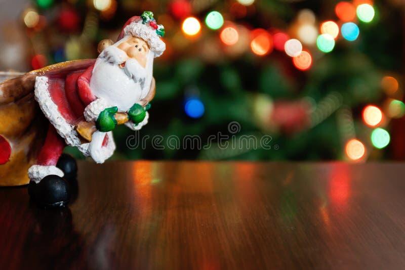 Santa Claus toy brings Christmas tree at blue snowy night bokeh royalty free stock images