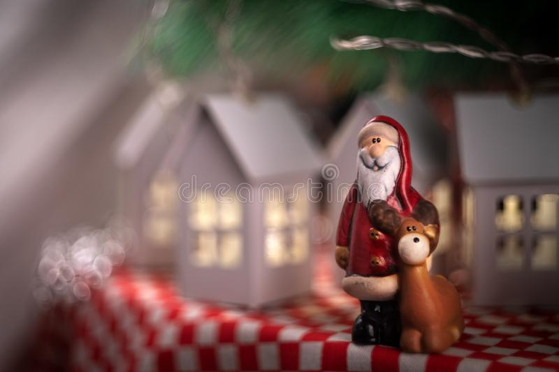 Santa claus toy with his deer rudolf. On the background of New Year`s garland of houses royalty free stock image