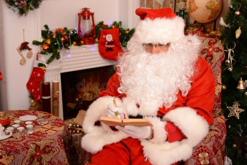Santa Claus tradicional comprueba su lista en un cuaderno foto de archivo libre de regalías