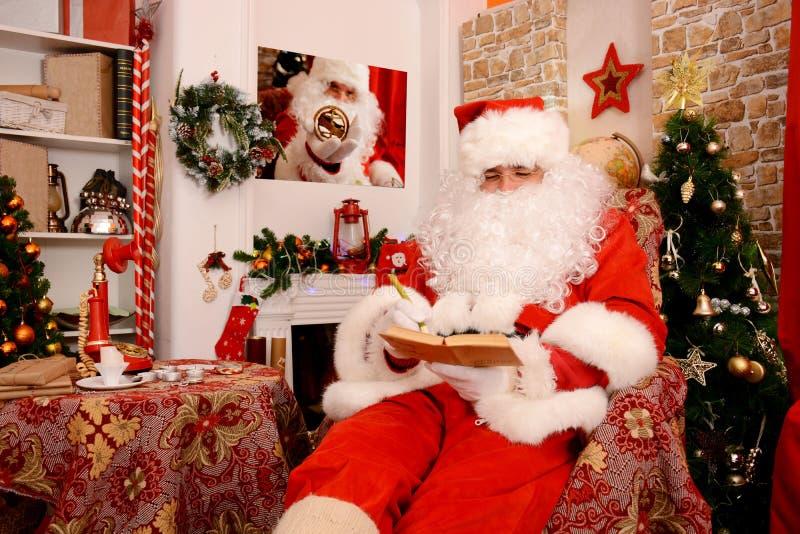 Santa Claus tradicional verifica sua lista em um caderno fotografia de stock royalty free