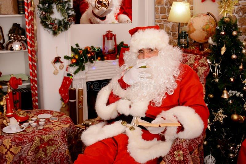 Santa Claus tradicional verifica sua lista em um caderno imagem de stock royalty free