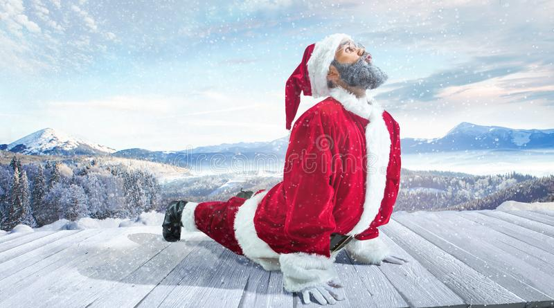 Santa Claus with traditional red white costume in front of white snow winter landscape panorama stock image