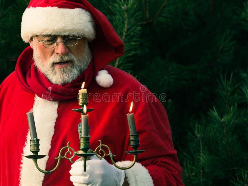 Santa Claus traditionnelle dans la forêt foncée de pin avec le chandelier photographie stock libre de droits