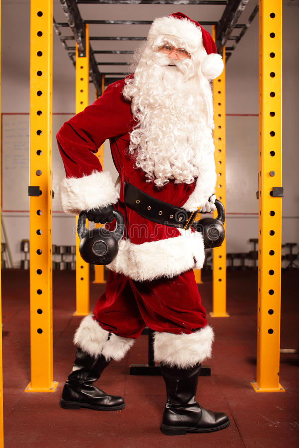 Santa Claus training before Christmas in gym - kettlebells. Santa Claus training before Christmas in gym with kettlebells royalty free stock photo