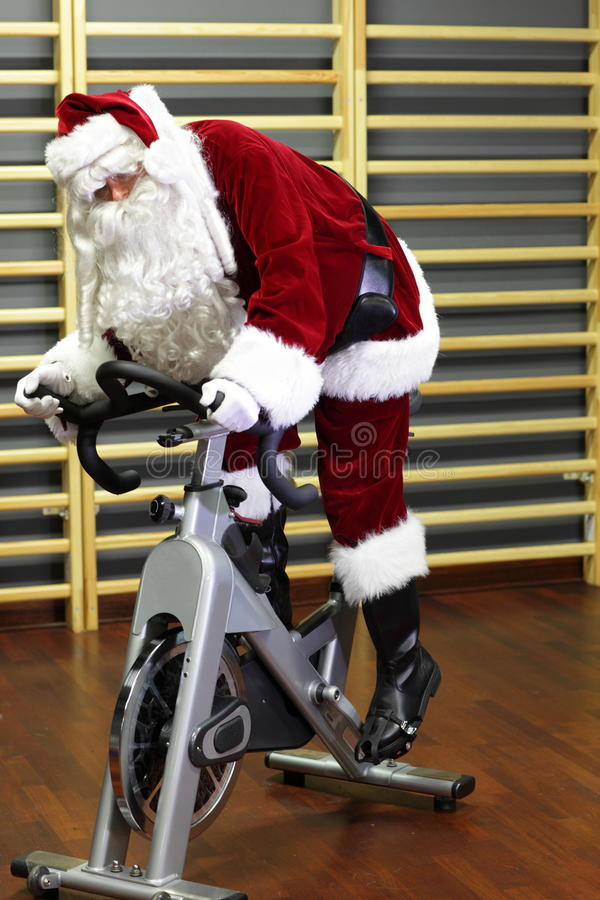 Santa Claus training on exercise bikes at the gym stock images