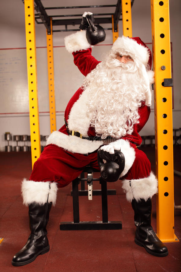 Santa Claus-Training vor Weihnachten in der Turnhalle - kettlebells stockfotografie