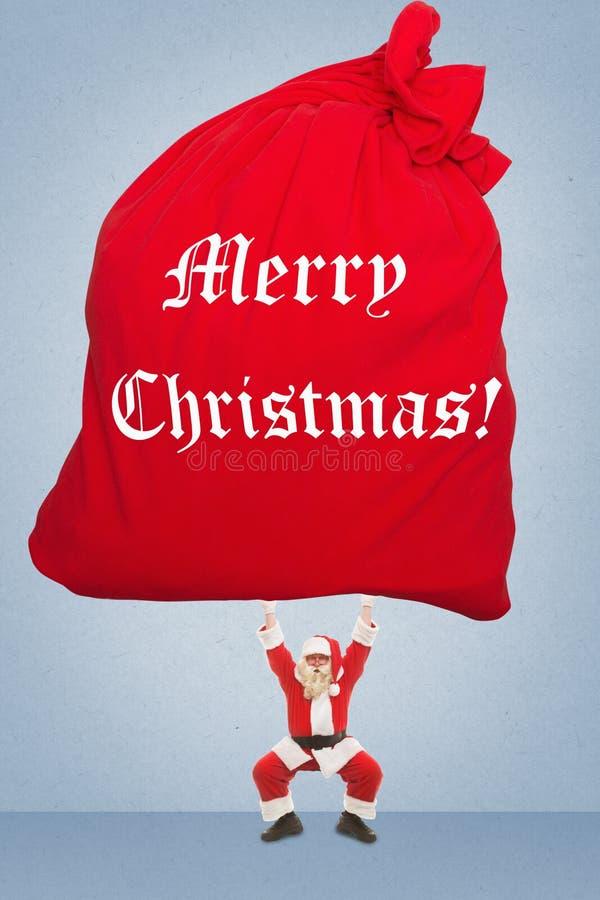 Santa Claus treina para levantar o saco muito pesado com presentes fotografia de stock royalty free