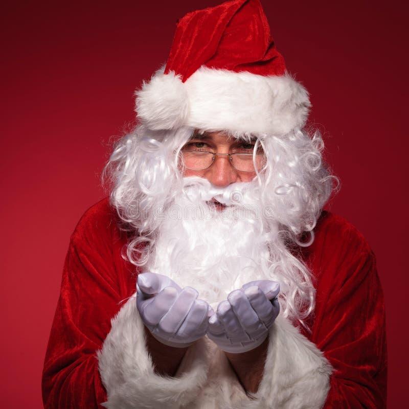 Santa Claus trzyma coś na jego rękach fotografia stock